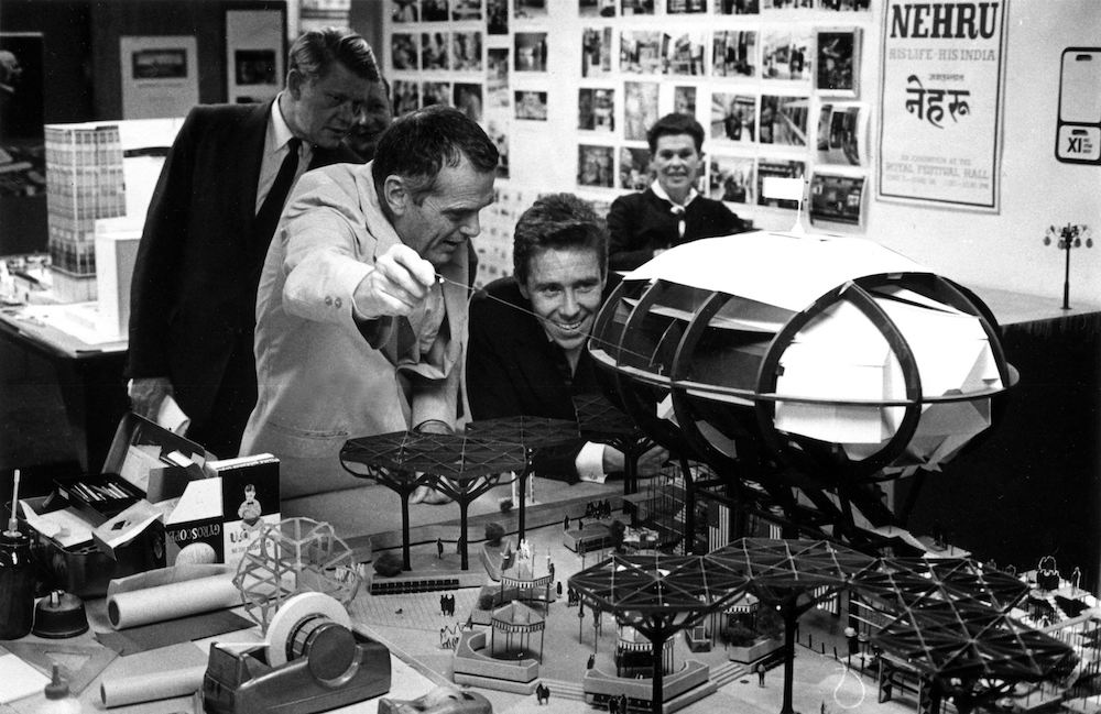 The World of Charles and Ray Eames. Charles shows Antony Armstrong_Jones model of I.B.M. Pavilion for NY Worlds Fair. © Eames Office LLC